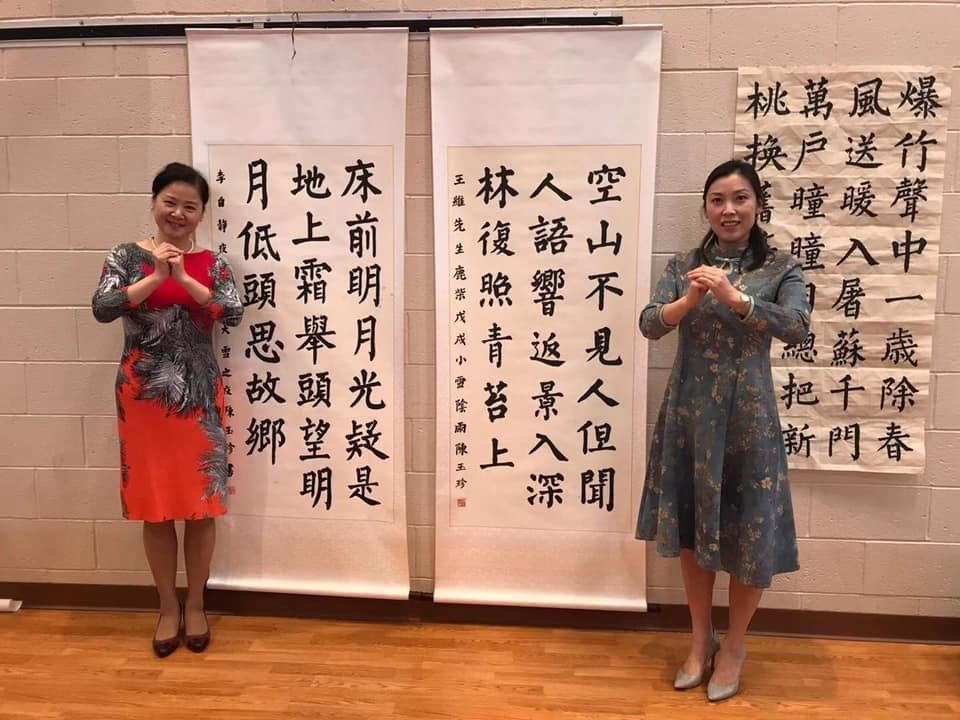 Two women stand in front of tapestries covered in Chinese characters